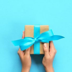 woman-arms-holding-gift-box-with-blue-ribbon-color-top-view_79075-2925